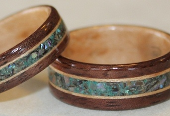 Walnut wood rings with Birds eye Maple liners.  Inlaid with Paua Shell and Eilat stone and bordered by narrow birds eye maple. Touch Wood Rings